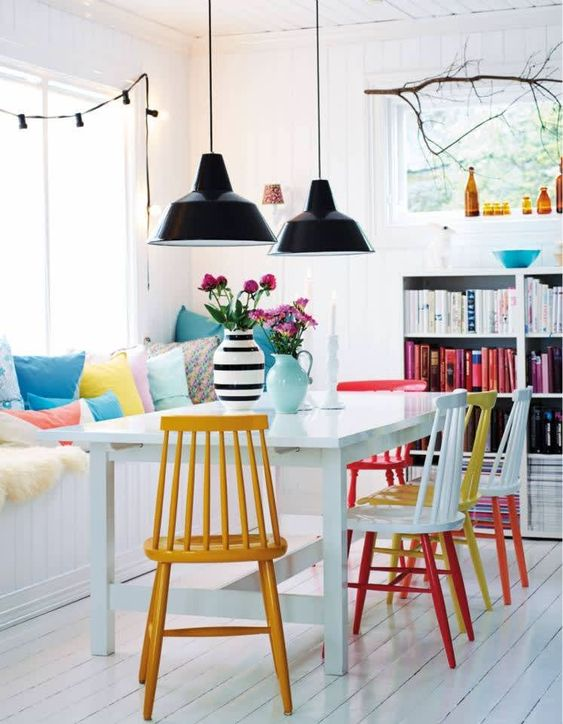 a neutral dining space is spruced up with colorful printed pillows and bright chairs that make a statement