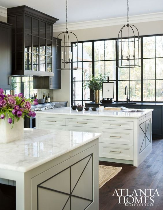 a vintage kitchen with two neutral kitchen islands with white stone countertops and lots of storage units inside