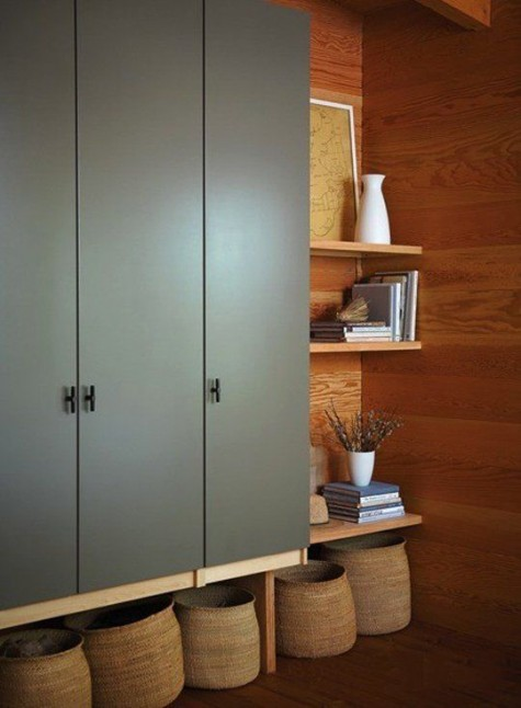 an IKEA Pax wardrobe in olive green, mounted on the wall and with open shelving