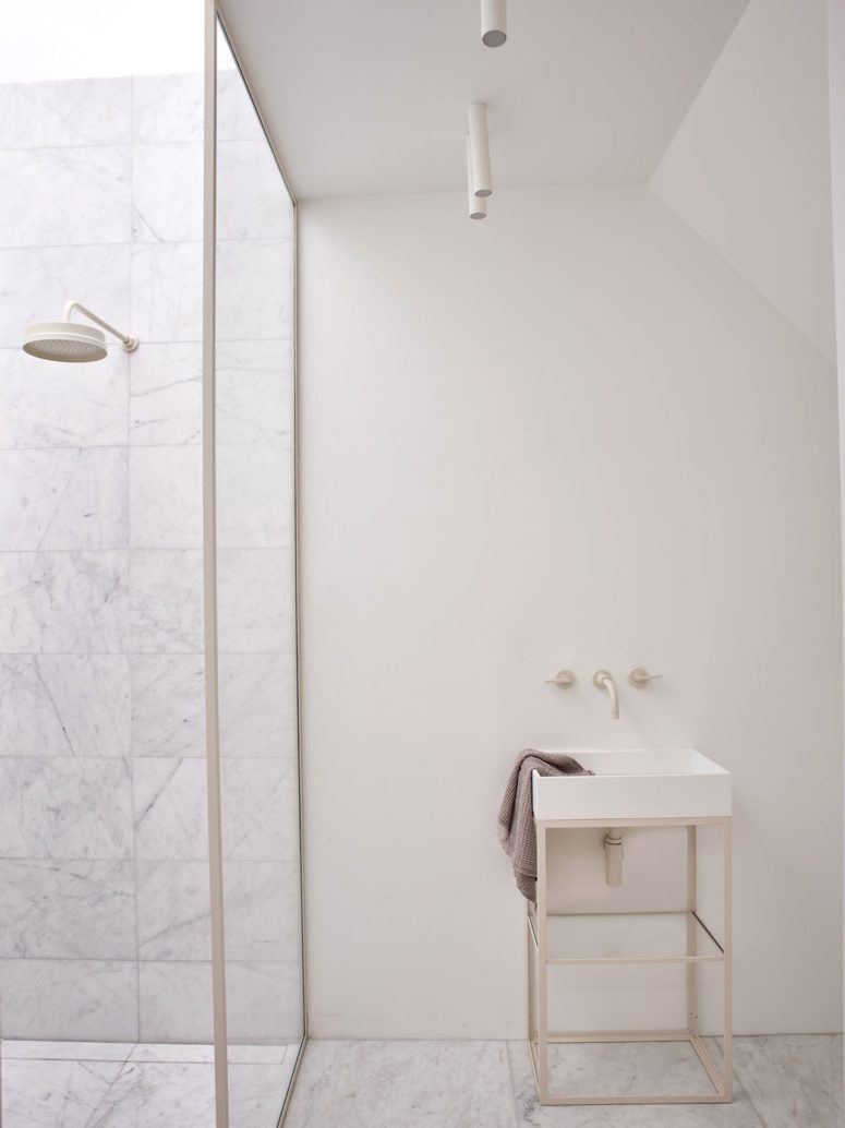 The bathrooms are done in neutrals, with marble and matte walls