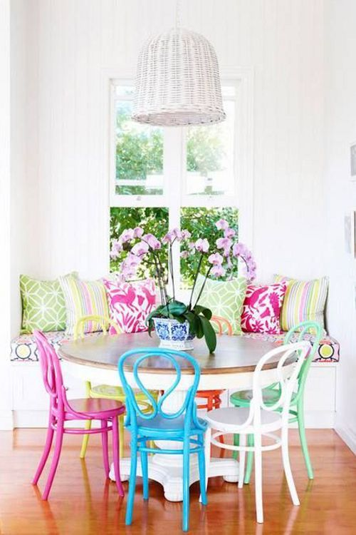 a bright dining space with super bright pillows and colorful chairs looks fun, cheerful and colorful