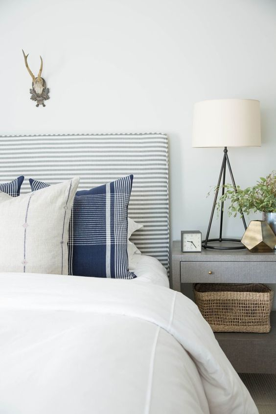 a cool striped grey and white upholstered headboard is a nice fit for many bedrooms including this rustic one