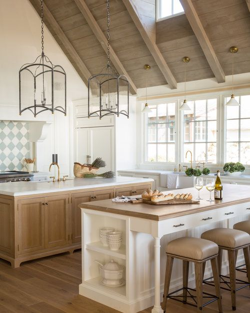 a neutral rustic kitchen with two kitchen islands that match, one for cooking and another for meals