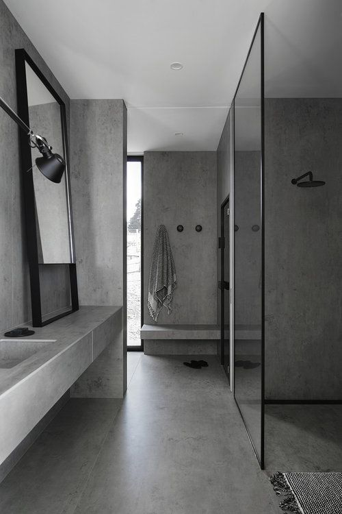 a concrete bathroom done with only concrete. tiles and glass plus touches of black