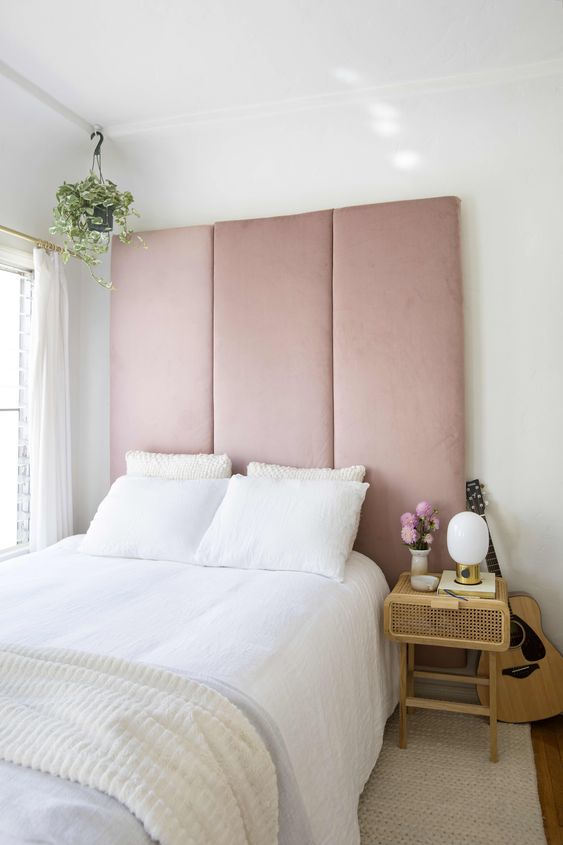 a statement blush pink upholstered headboard is a tender and sweet statement that takes over the whole space