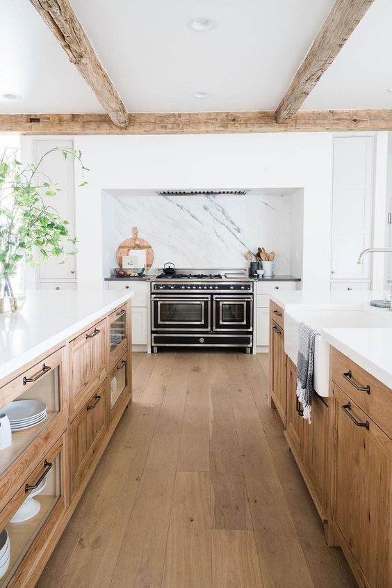 two large wooden kitchen islands with open and closed storage and white countertops look very stylish