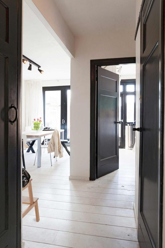 a fully neutral and light filled space gets some drama from black doors here and there