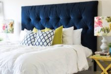 15 a navy tufted headboard is the main centerpiece of the bedroom, it brings color and makes a statement