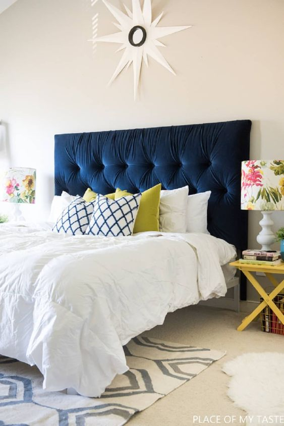 a navy tufted headboard is the main centerpiece of the bedroom, it brings color and makes a statement