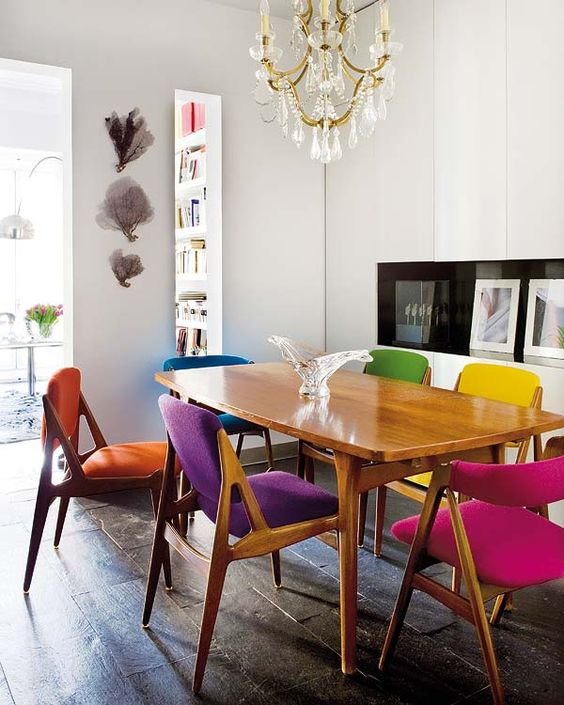 a stylish and cozy mid-century modern dining room with matching yet differently upholstered chairs