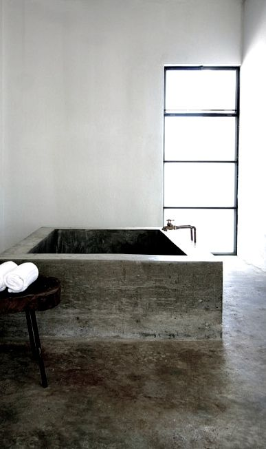 an ultra-minimalist bathroom done in concrete with a large soaking bathtub and white concrete walls