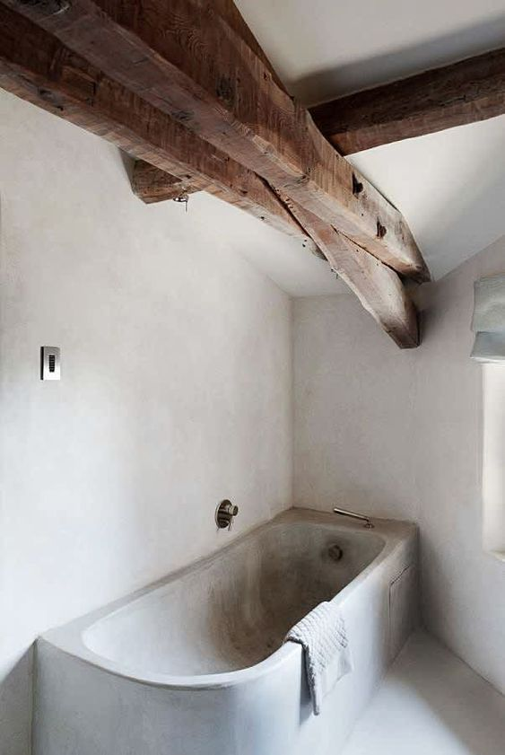 a concrete bathroom with white walls and a grey bathtub plus wooden beams on the ceiling