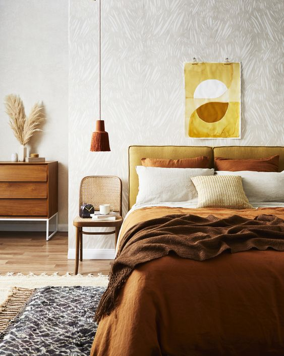 a fall-colored earthy bedroom in ocher, yellow, mustard and rust shades and with wood and rattan