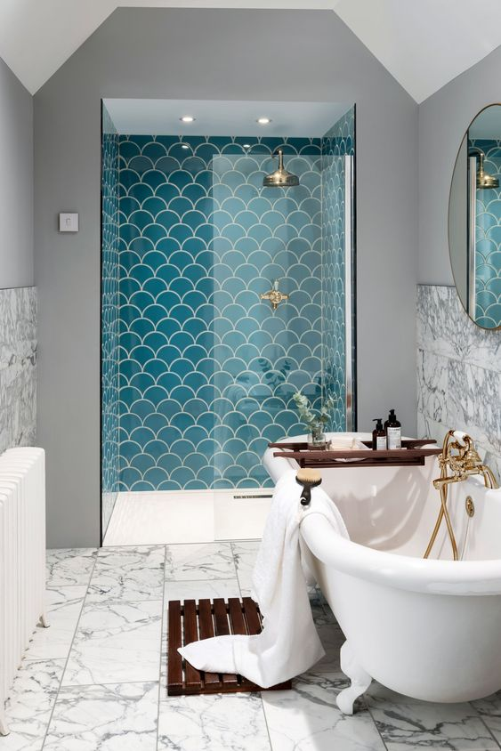 a shower space done with turquoise scallop shaped tiles that make it stand out a lot