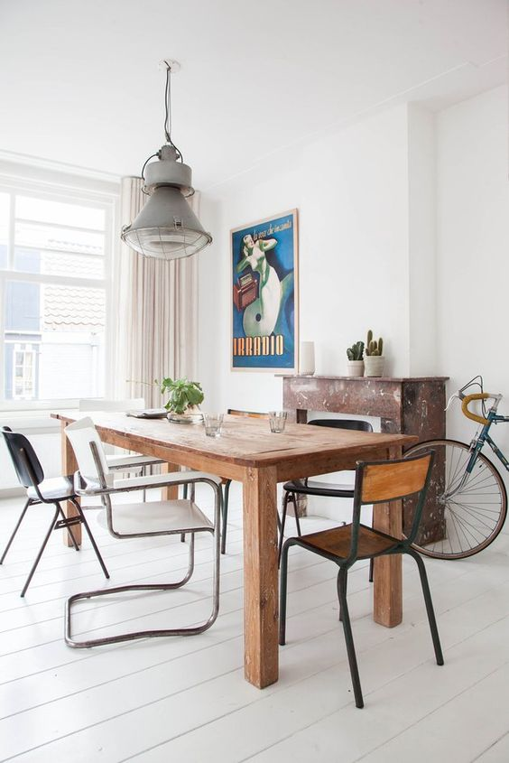 a chic dining space with a wooden table and mismatching chairs that make it evne more inviting and whimsy