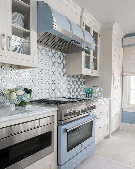 a light blue cooker and hood match the color of the walls and delicately infuse the neutral space with color