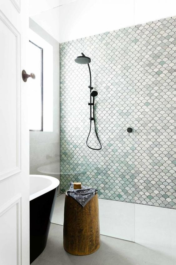 a neutral bathroom with a shower space done with aqua-colored scallop tiles that make it stand out