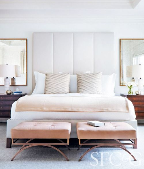 a statement white upholstered headboard and little pink stools to create a soft feel in the space