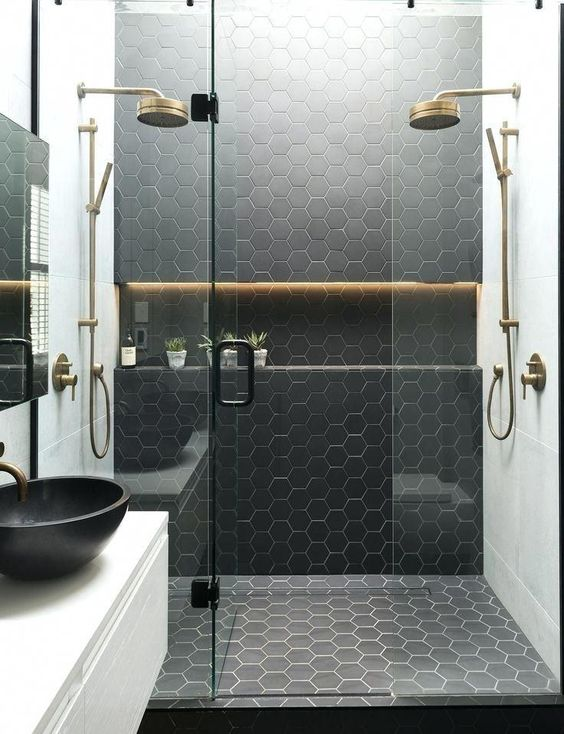 a black and white bathroom with hexagon tiles in the shower space and brass touches for more elegance