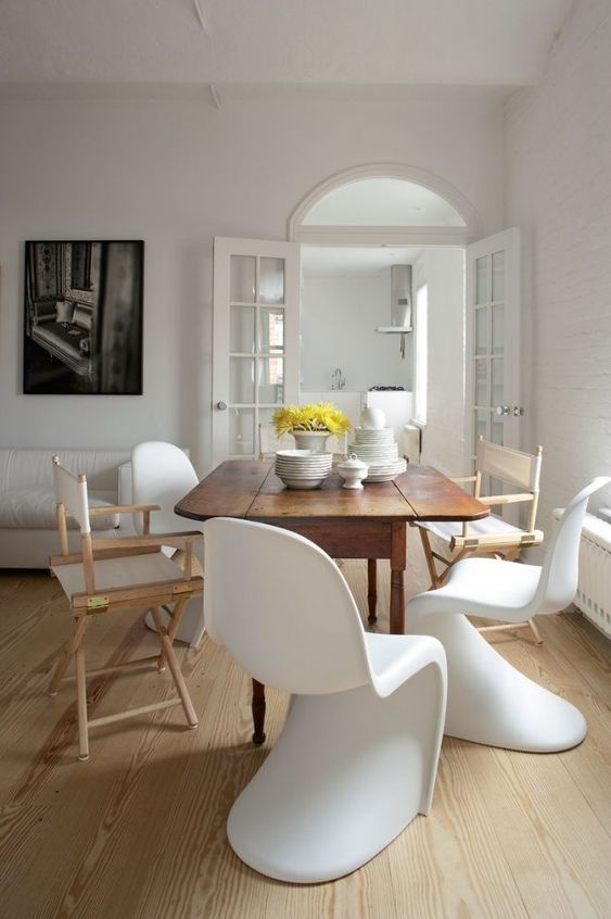 a chic dining room with a wooden table and totally mismatching chairs in the same color scheme