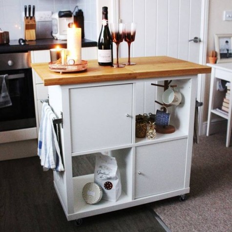 an IKEA Kallax turned into a mobile kitchen island with a wooden countertop and some closed compartments