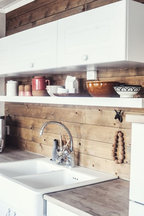 boldly rock a wooden kitchen backsplash like here to add a cozy touch to the space