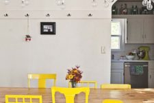 20 a dining room with a long wooden table and a number of mismatching chairs done in the same shade of yellow