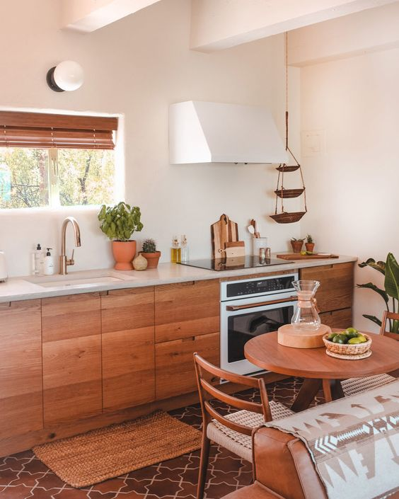 a warming and welcoming kitchen with wooden furniture, wooden shutters and natural greenery in pots