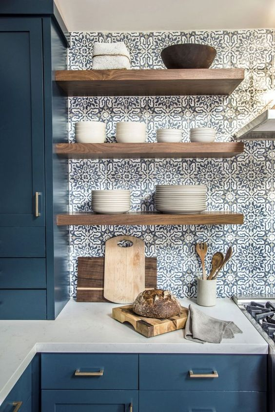 light-colored wooden open shelves stand out in  the blue mosai tiles and add a warm touch to the space