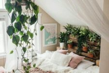 23 a crate shelf with potted plants and greenery and a cage with vines over the bed for a boho feel