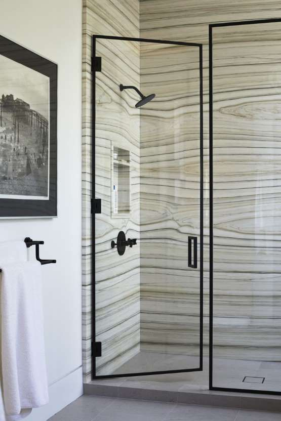 a shower space done with unique marble in greys and greens with stripes looks really wow