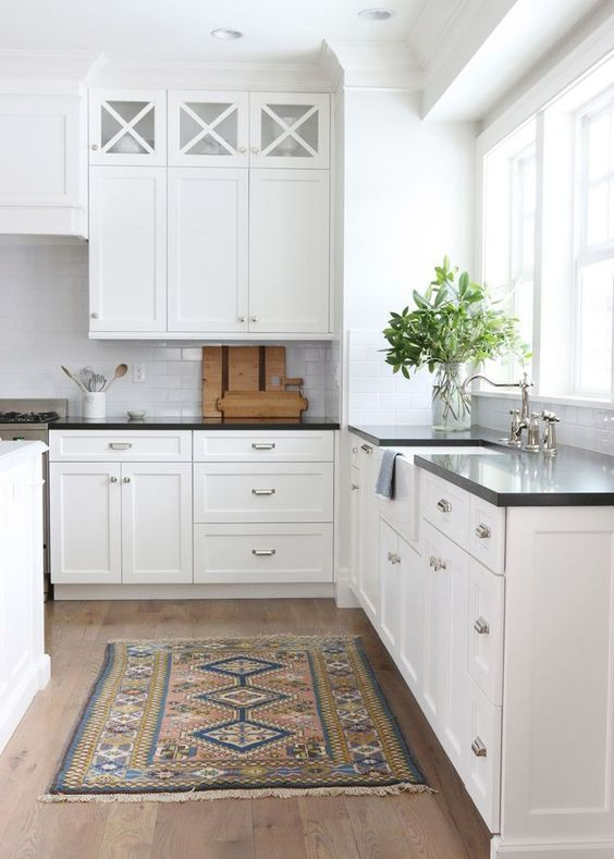 a classic white kitchen with black countertops that create interest due to the contrast they bring