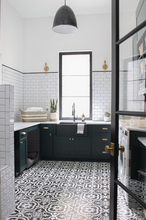 a gorgeous black and white farmhouse kitchen with a printed tiled floor that adds interest to the space