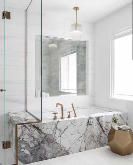 a neutral bathroom with a unique marble clad bathtub and brass fixtures for a more chic look