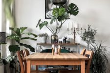 25 greenery in vases and pots and a green chair make the monochromatic dining room brighter and fresher