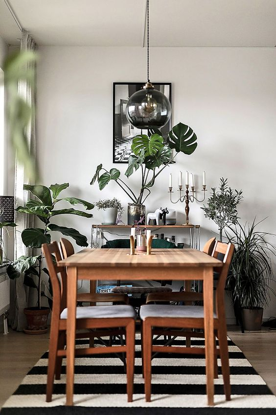 greenery in vases and pots and a green chair make the monochromatic dining room brighter and fresher