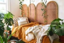 25 potted statement plants and some vines hanging over the bed make the bedroom feel tropical