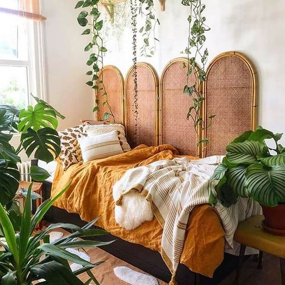 potted statement plants and some vines hanging over the bed make the bedroom feel tropical