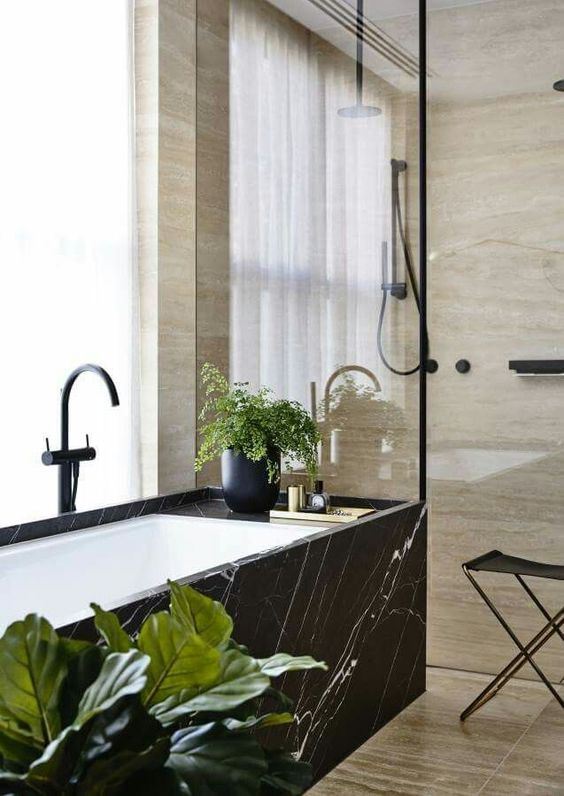 a black marble clad bathtub stands out a lot in a neutral warm-colored space