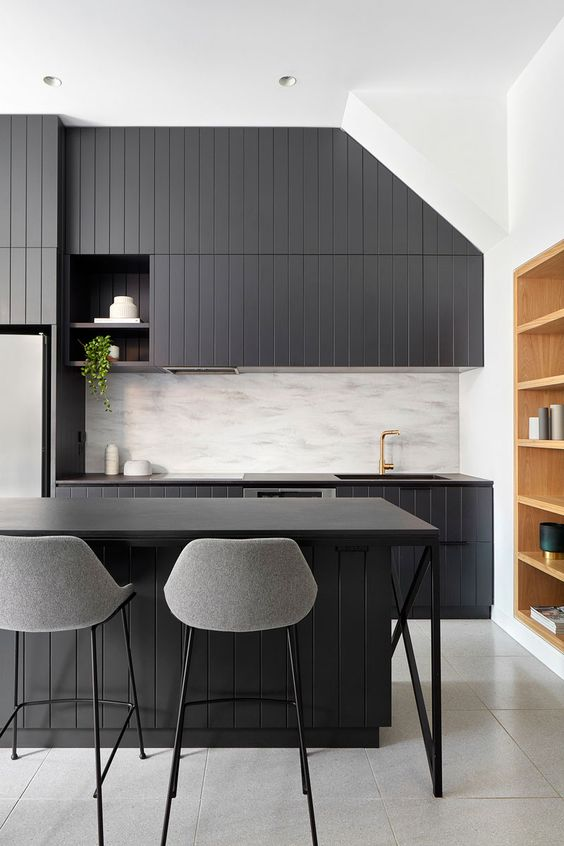 a dark kitchen with dark countertops is a stylish idea and a neutral backsplash adds contrast to the space