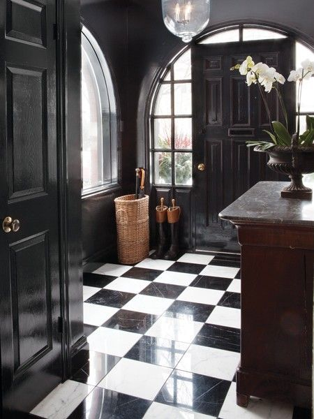 a refined and chic black and white entryway with a checked floor and black doors looks really wow