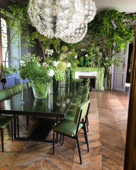 a refined dining room refreshed with a green fireplace and chairs and lots of greenery arrangements in vases and pots