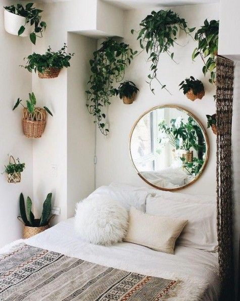 potted greenery in baskets attached to the wall over the bed refresh the space and make it bolder