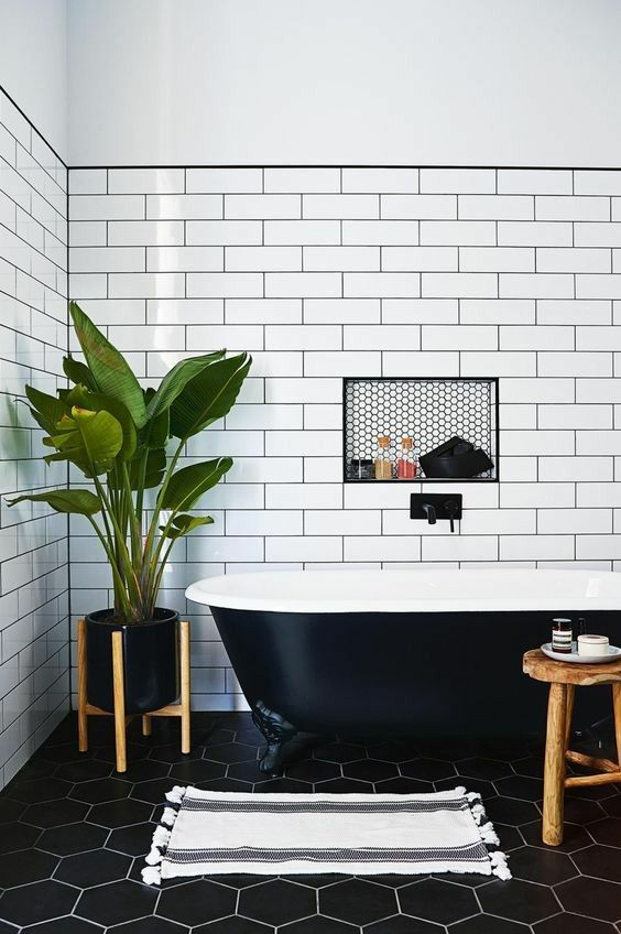 a chic bathroom with a black retro free-standing bathtub that matches the space perfectly