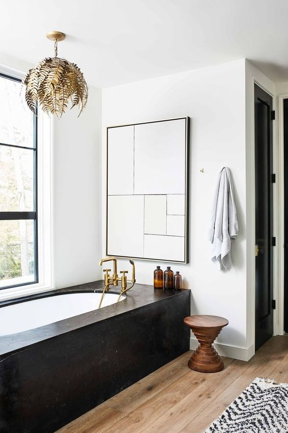 a refined bathroom with a black clad bathtub that is the centerpiece of this space