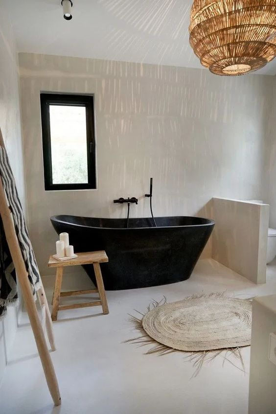 a minimalist meets boho bathroom with a black stone bathtub and some touches of jute and wood