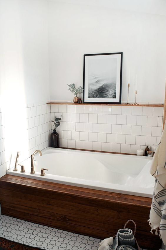 a cozy bathroom niche done with white tiles and a bathtub clad with stained wood