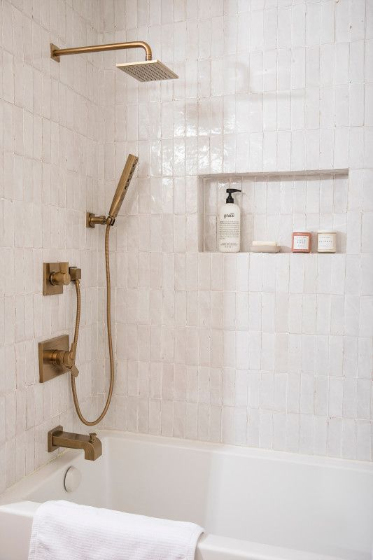 modern brass fixtures in the neutral bathroom make it chic and refined