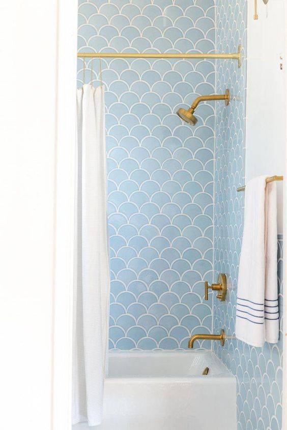 light blue scallop tiles and brass fixtures create a cool and chic combo for a bathroom