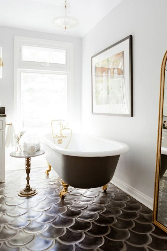brass legs and a mirror frame spruce up the monochromatic space and make it brighter and bolder